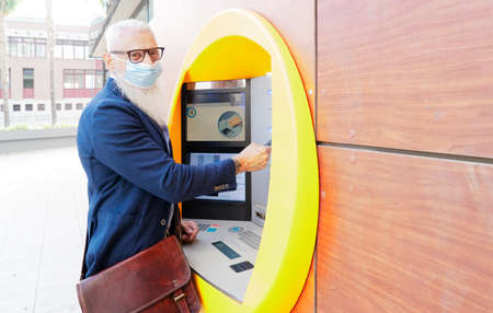 Senior man with ATM, Happy mature male using bank cash machine wearing mask on his face - Concept of business, banking account and new normal lifestyle people
