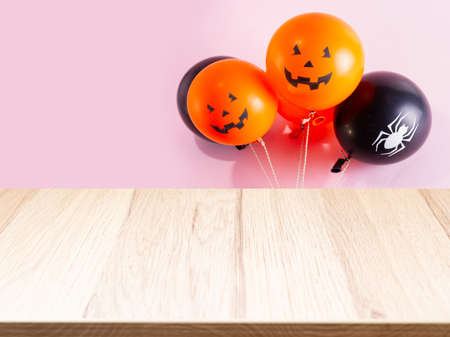 Halloween scene with balloons with spooky faces on pink background, product display on wooden board
