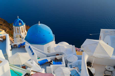 traditional greek village Oia of Santorini, with blue domes of churches and village roofs, Greece