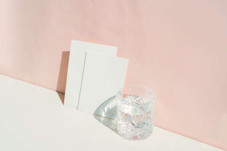 summer stationery mock-up scene. Blank business card and glass of clear water on beige textured table background
