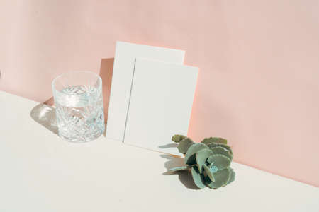 summer stationery mock-up scene. Blank business card, succulent and glass of clear water on beige textured table background.
