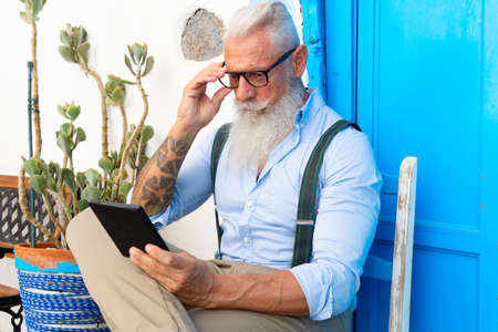 Senior hipster man is reading e-book, happiness, technology and elderly lifestyle people concept