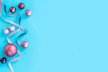 Christmas flat lay scene with festive ribbons and balls christmas decorations on all aqua blue background with copy space