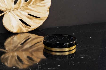 Minimal modern product display on black and golden background with podium, luxury 20s style