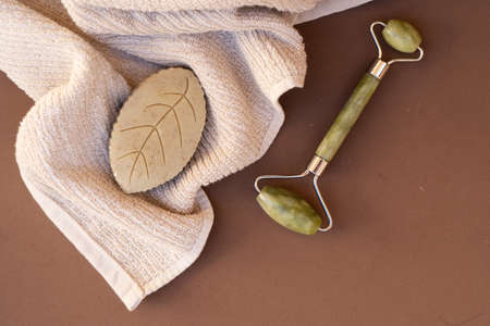 gua sha, face massage roller made of natural stone, home spa concept, earth tones background Imagens