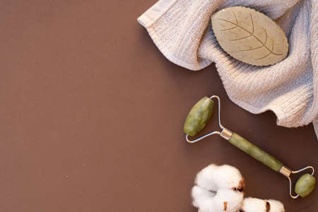 gua sha, face massage roller made of natural stone, home spa concept, earth tones background, copy space Imagens