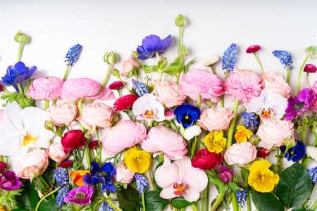 花组成。边界由玫瑰,毛茛属,蝴蝶花和兰花花在白色背景开花。平躺,顶视图场景。
