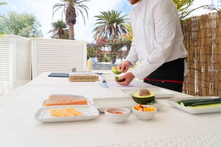 Male chef in uniform peeling avocado for sushi