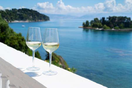 Two glasses of white wine with Corfu seascape in background Foto de archivo