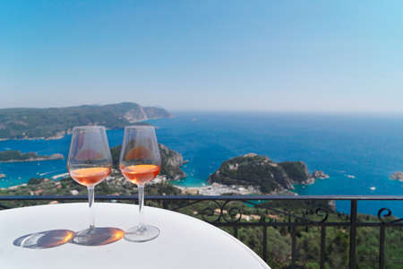 Two glasses of kumquat liqueur wine with Corfu seascape in background