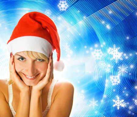 Beutiful girl in Christmas hat on abstract winter background photo