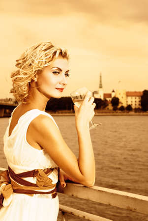 Beautiful blond girl drinks champagne near the river at sunset time Stock Photo - 2181415