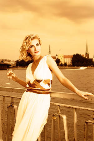Beautiful blond girl drinks champagne near the river at sunset time Stock Photo - 2181414