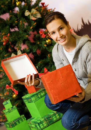 Teenager girl with gift boxes, Christmas three behind her Stock Photo - 2181411