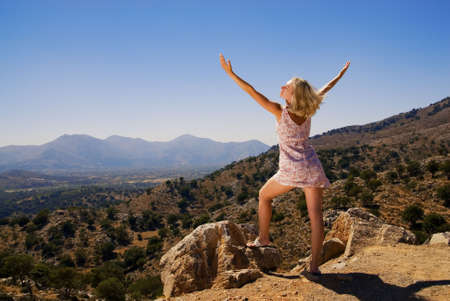 legs wide open: Beautiful girl standing on a mountain with her hands wide open Stock Photo
