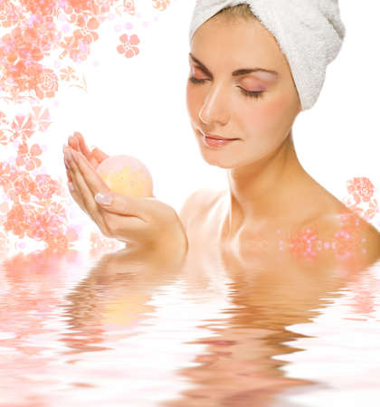 Beautiful young woman with aroma bath ball reflected in rendered water photo