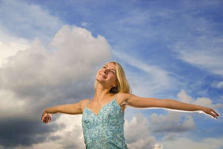 arms wide: Bella ragazza bionda con braccia spalancate oltre blu cielo poco nuvoloso  Archivio Fotografico