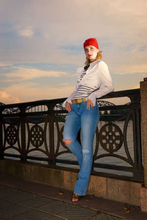 Beautiful young girl in red bandana over sunset sky