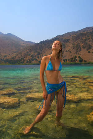 swimsuite: Beautiful blond girl stanging in crystal clear water