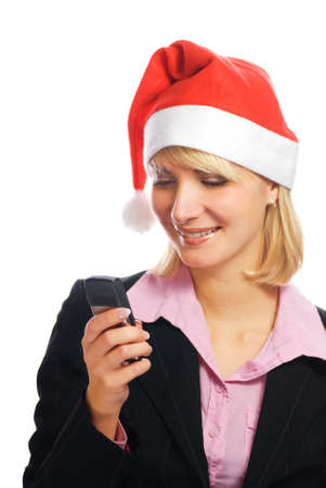 Beautiful business woman in Christmas hat typing message on her mobile phone photo