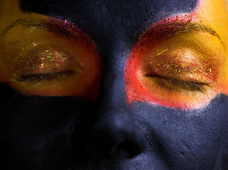 Portrait of a mysteus woman with artistic make-up on her face. Isolated on black background Stock Photo - 2202337