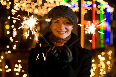 Beautiful happy girl with  fireworks on abstract blurred background photo