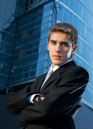 Young confident business man posing in front of office building photo