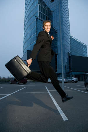 Happy business man running home after work Stock Photo - 2222103