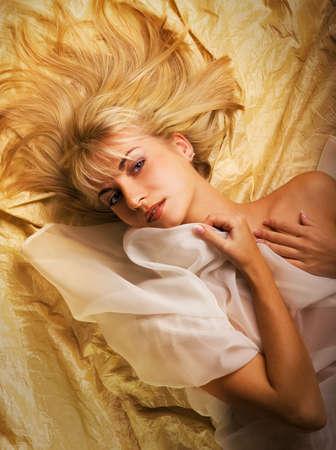Beautiful blond girl lying on a luxury golden fabric Stock Photo - 2241387