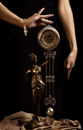 Yong girls hands and antique clock photo