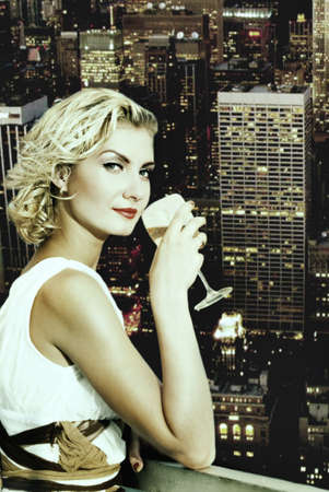 megapolis: Beautiful blond girl drinks champagne on a skyscraper in megapolis Stock Photo
