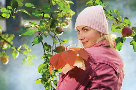 Beautiful girl with autumn leaves near the apple tree and blue foggy background behind her Stock Photo - 2262172