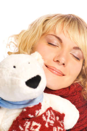 Beautiful blond girl in winter clothing with a white polar bear photo