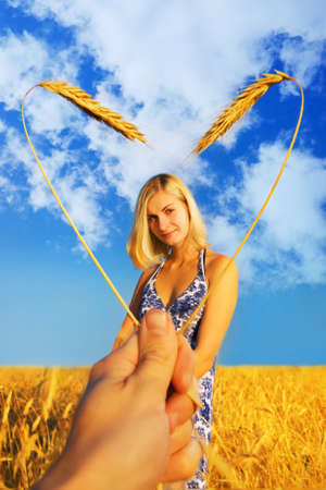 Beautiful girl standing in the wheat field and heart shaped border around her photo