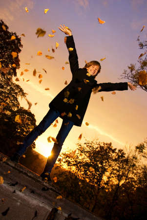 Young girl throwing autumn leaves at sunset time photo