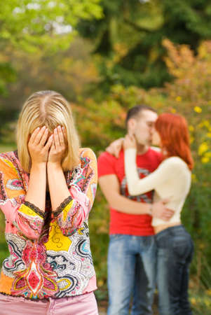 unfaithfulness: Crying girl and kissing couple on a background Stock Photo