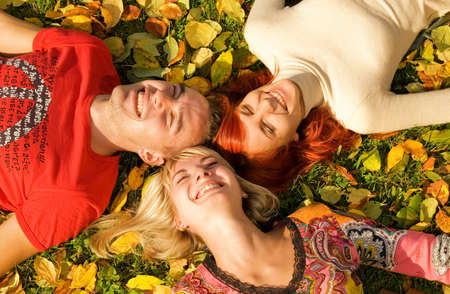 Three friends lying on autumn leaves photo