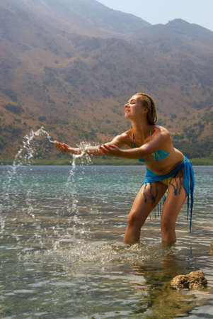 Beautiful blond girl playing with water in a lake photo