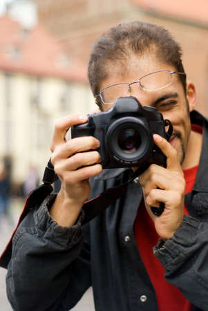 photography session: Handsome guy with a digital camera (shallow DoF, focus on eye)