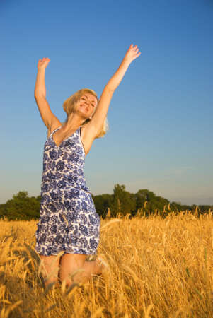 Beutiful blond girl jumping in the wheat field photo