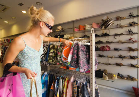 Blonde woman buying clothes in a shop