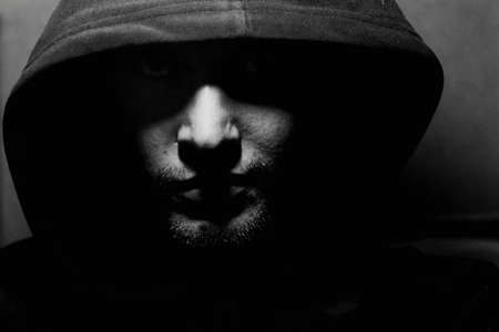 sinister: Monochrome picture of a guy in a hood Stock Photo