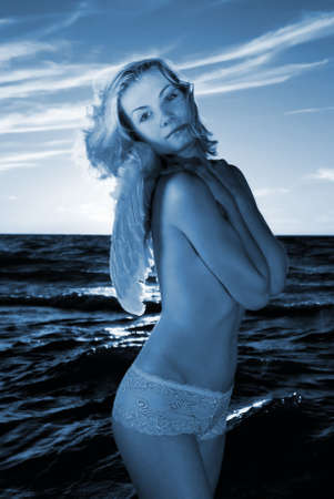 Angel girl in a sea at sunset time (toned in blue) Stock Photo - 2282349