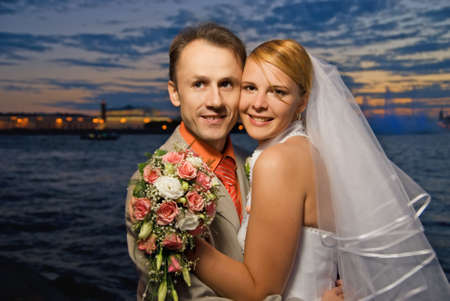 Just married couple near the river at sunset time photo