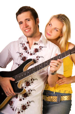 Young musician plays guitar and beautiful blond girl stands nearby photo