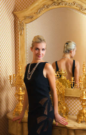 defiant: Beautiful blond girl stands near the mirror