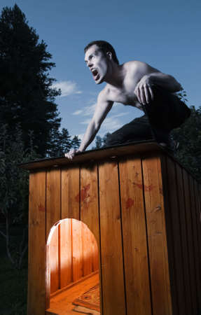 Scary man sitting on kennel and turning into werewolf photo