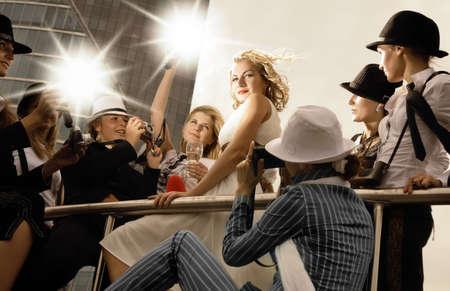 Mooie blonde meisje kijkt op een superster poseren en veel fotografen rond haar foto's te