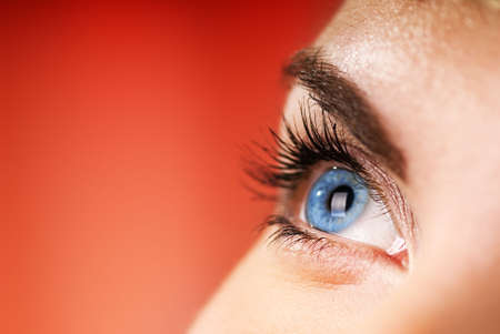 eye care: Blue eye on red background (shallow DoF) Stock Photo
