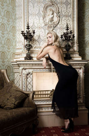 Beautiful blond girl near the fireplace